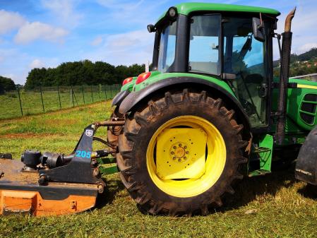 Tractor con desbrozadora de arrastre